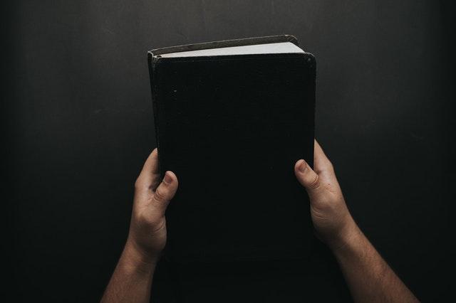 biblia w czarnej oprawie w dłoniach
