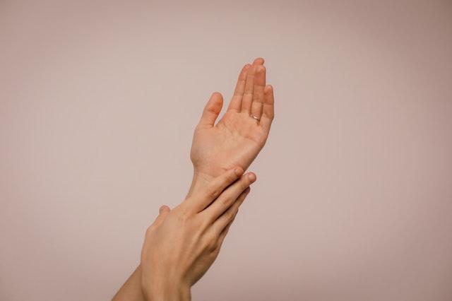 ręce,które się dotykają na jasno różowym tle