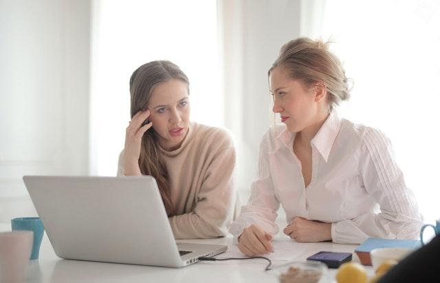 dwie kobiety siedzące przed komputerem