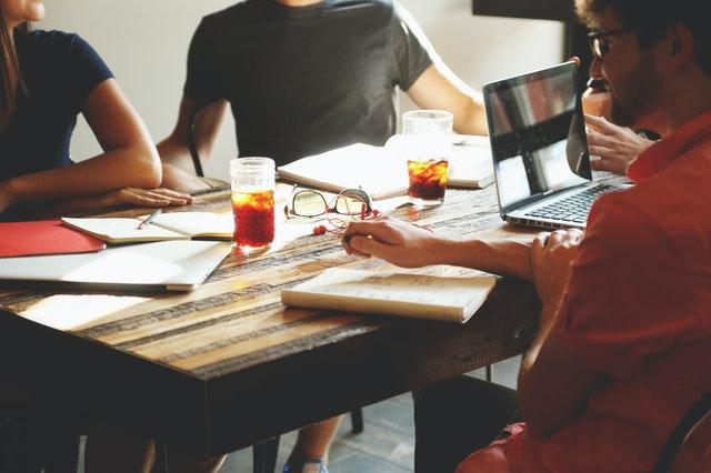 grupa ludzi siedzi przy drewnianym stole, mając przed sobą zeszyty i kalendarze