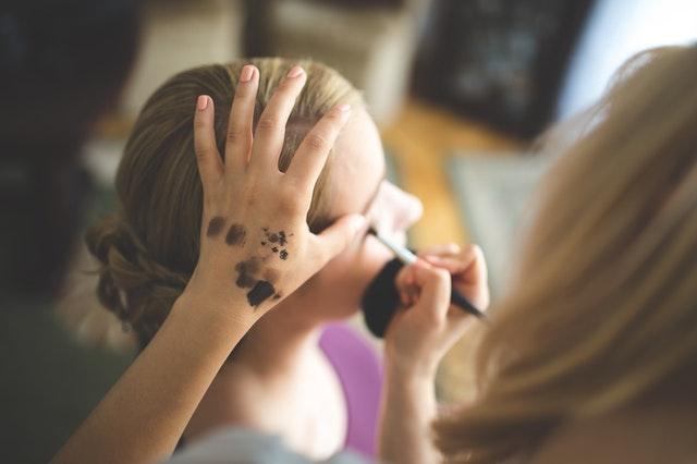 wizażystka maluje młodą kobietę