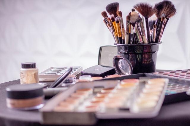 cienie do powiek, pędzle do makijażu i puder na stole