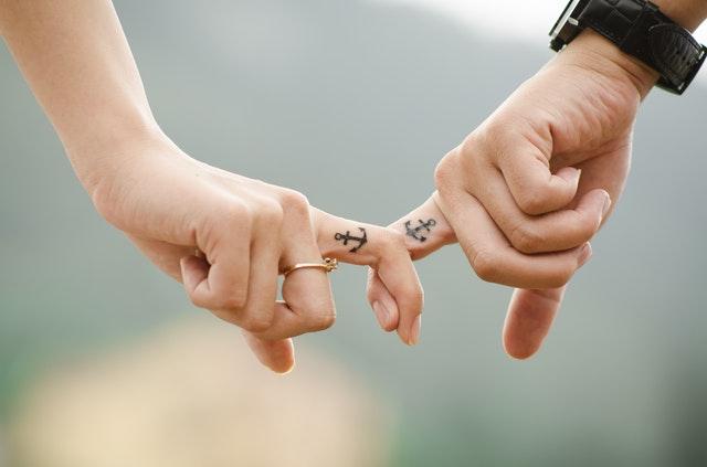 dwa palce z dwóch dłoni, które łapią się i widać tatuaże kotwice