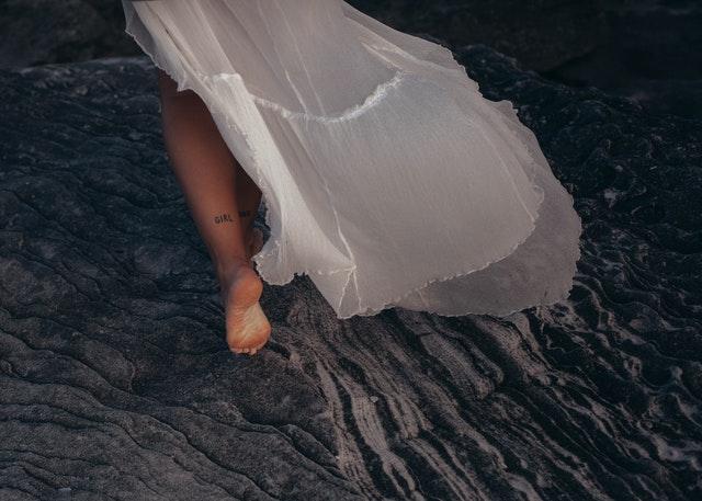 biała spódnica wieje na figurze kobiety odsłaniając jej nogi i tatuaż na dole nogi