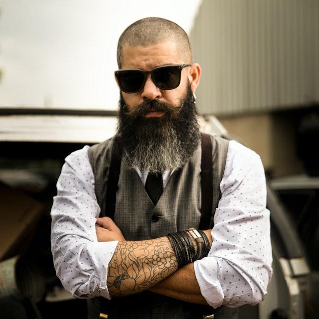 mężczyzna w okularach, długich włosach i tatuażach na rękach