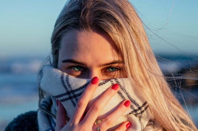 blondynka w rozpuszczonych włosach przytrzymuje szal w kratę dłonią z czerwonymi paznokciami