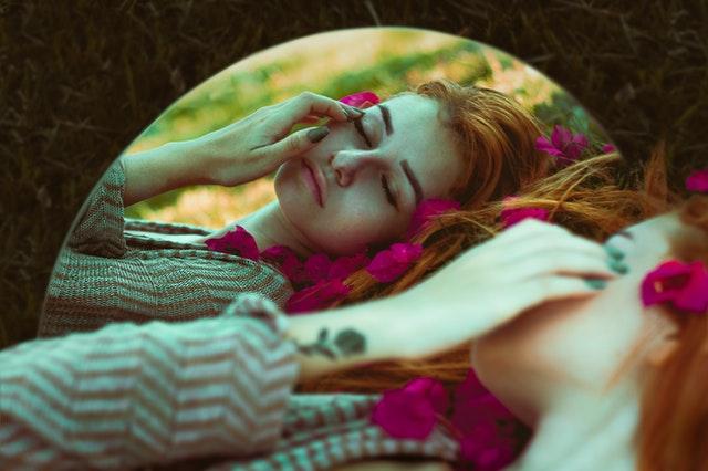 rudowłosa kobieta spogląda w lustro ukazując tatuaż na nadgarstku