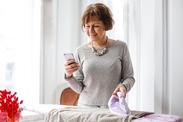 dojrzała kobieta w szarym swetrze spogląda w telefon przy desce do prasowania
