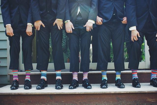mężczyźni w garniturach uchwyceni od pasa w dół podnoszący spodnie i pokazujący skarpety