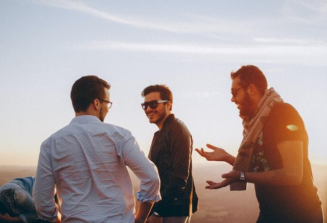 uśmiechnięci panowie stoją na zewnątrz przy zachodzie słońca