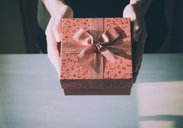 bordowy prezent trzymany w dłoniach