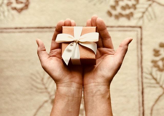 mały różowy prezent z kokardką na dłoniach