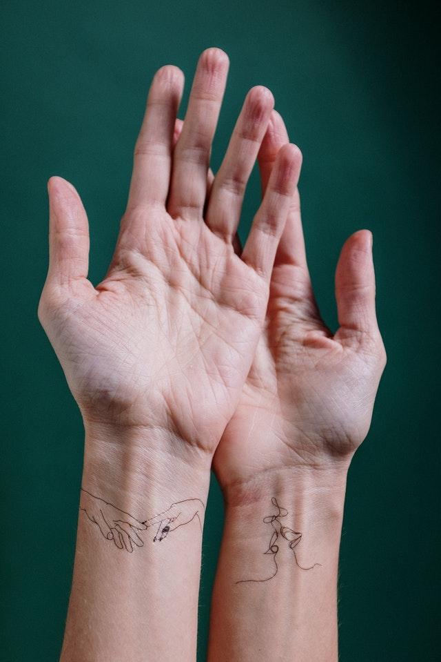 zaplecione ze sobą dłonie z minimalistycznymi tatuażami na nadgarstkach