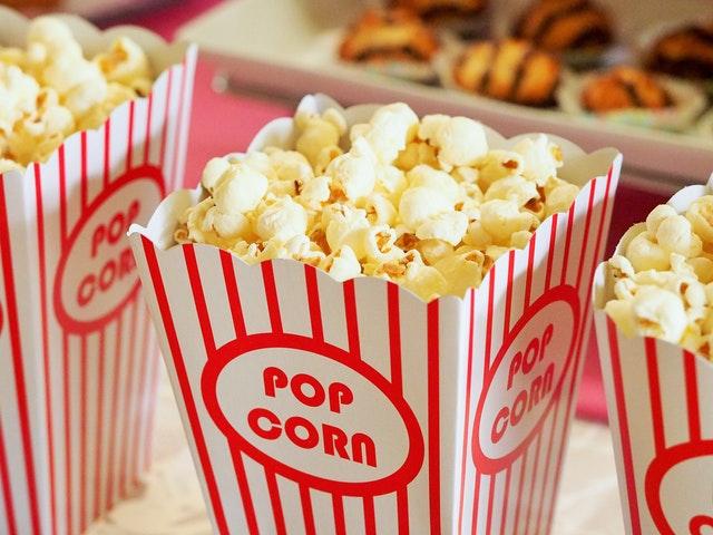 popcorn włożony w papierowe opakowanie w paski biało-czerwone