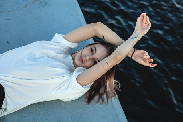 kobieta w białej koszuli wyciągnięta nad wodą z uniesionymi rękoma