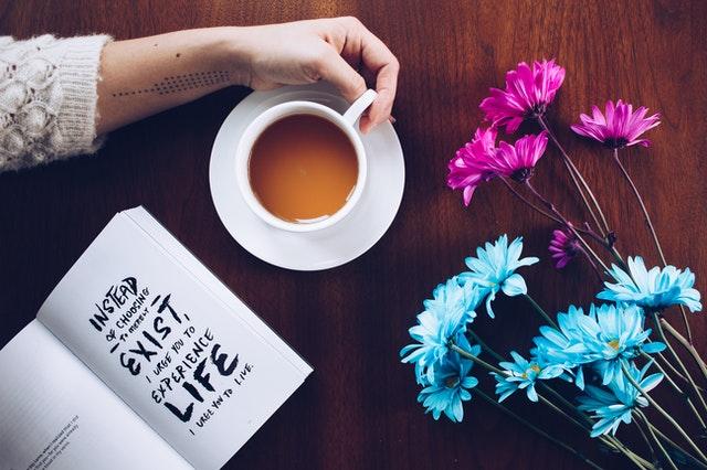 dłoń trzyma filiżankę a obok na stole leżą różowe i białe kwiaty