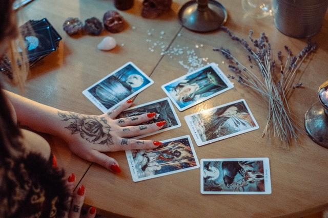 zdjęcia polaroidowe rozłożone na stole i na nich położona ręka z tatuażem