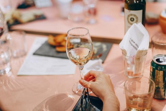 lampka wina na tle stołu z różowym obrusem