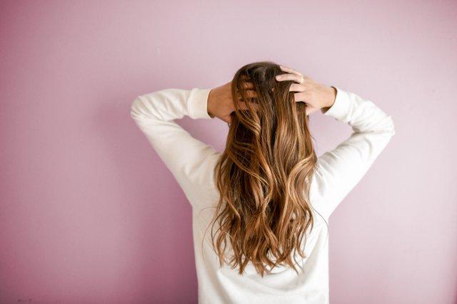 dziewczyna o kasztanowych włosach stoi tyłem na tle różowej ściany