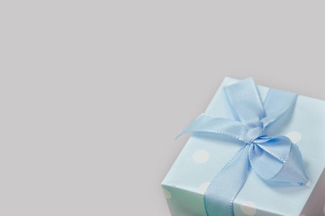 niebieskie pudełko w białe kropki z niebieską wstążką