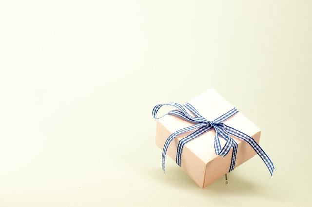 białe pudełko prezentowe owinięte niebieską taśmą