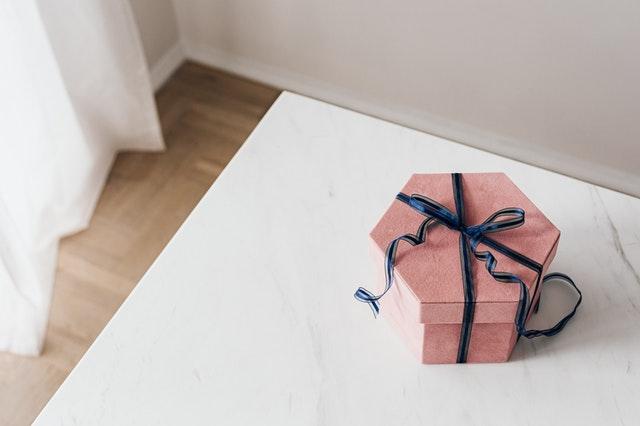 różowe pudełko z niebieską wstążką na białym stole