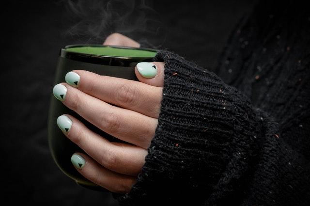 zielony manicure z kropką na tle kubka i ciemnego swetra