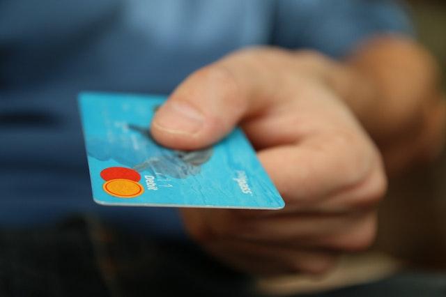 niebieska karta płatnicza w dłoni męskiej
