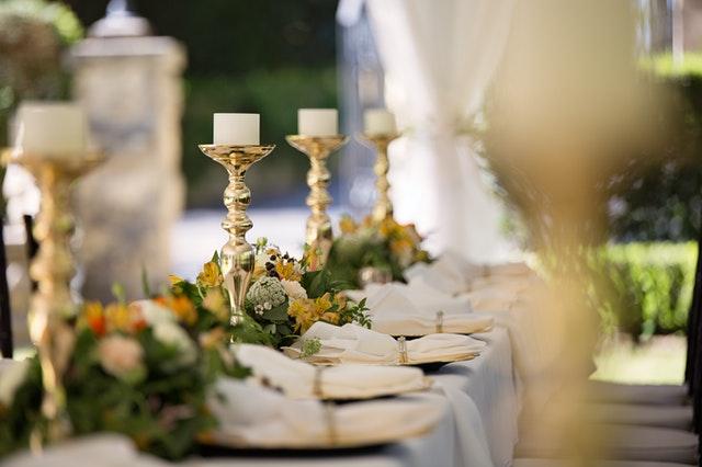 stół biesiadny ze złotymi świecami i kwiatami