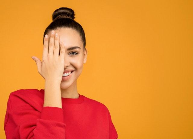 uśmiechnięta brunetka w spiętych włosach na tle pomarańczowej ściany