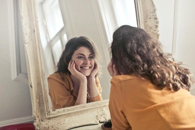 szatynka w rozpuszczonych włosach  uśmiecha się i patrzy w lustro