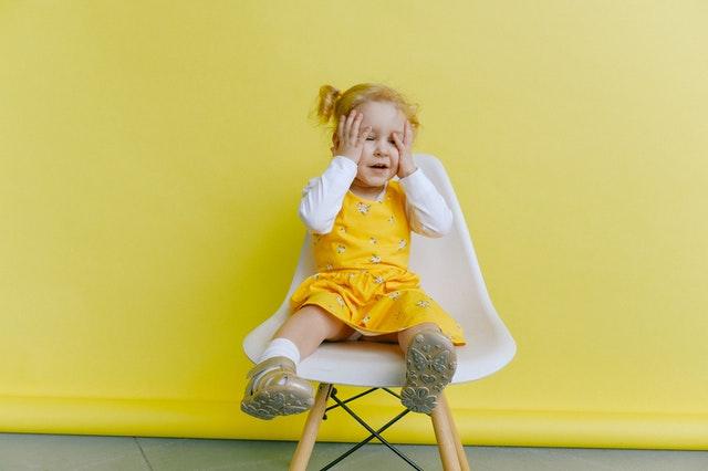 malutka dziewczynka w żółtej sukience siedzi na białym krzesełku na tle żółtej ściany
