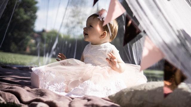 malutka dziewczynka siedzi w różowej sukience w opasce na główce