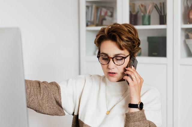 kobieta krótko ścięta w okularach rozmawia przez telefon