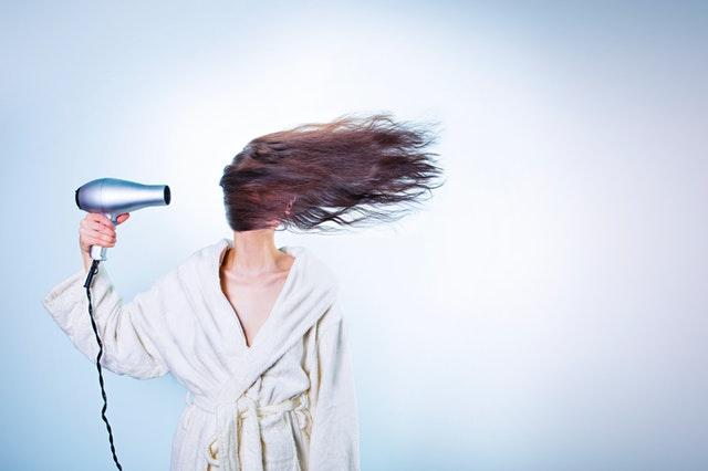 kobieta z długimi włosami w białym szlafroku suszy sobie włosy