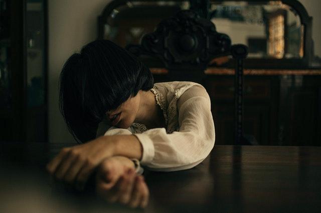 brunetka o włosach ściętych na boba opiera się na stole w białej koszuli