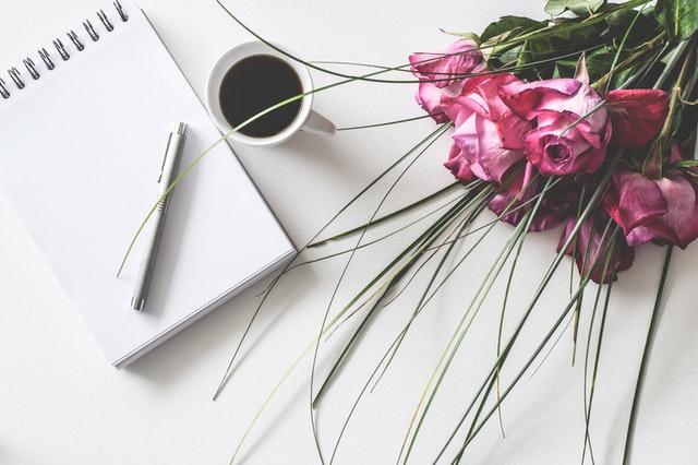 kartka papieru tuż obok kawy w białej filiżance i różowego bukietu
