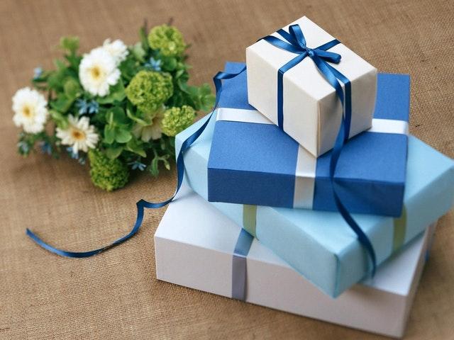 niebieskie pudełka z kokardami stoją na sobie a obok leży zielony bukiet z kwiatów