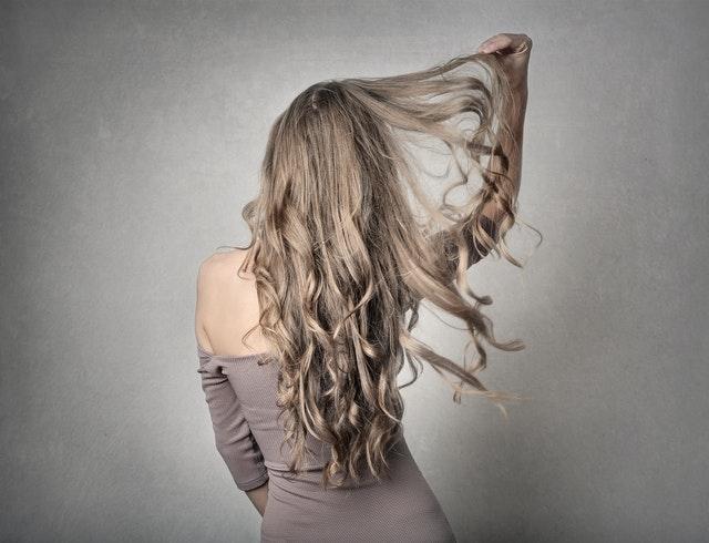 blondynka stoi tyłem w beżowej sukience i ma rozpuszczone włosy