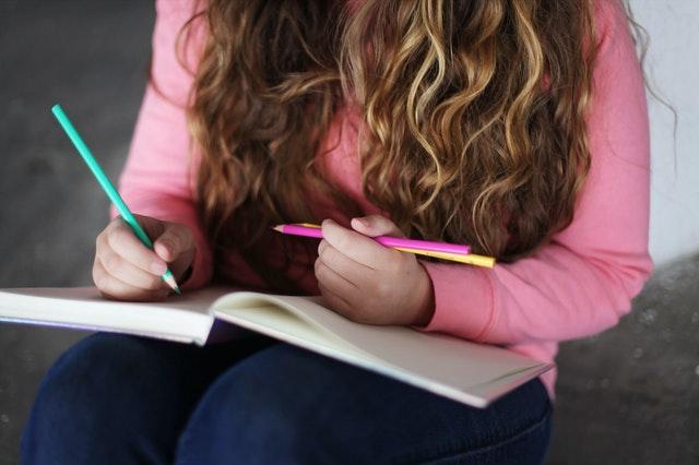 nastolatka w różowym sweterku i rozpuszczonych włosach