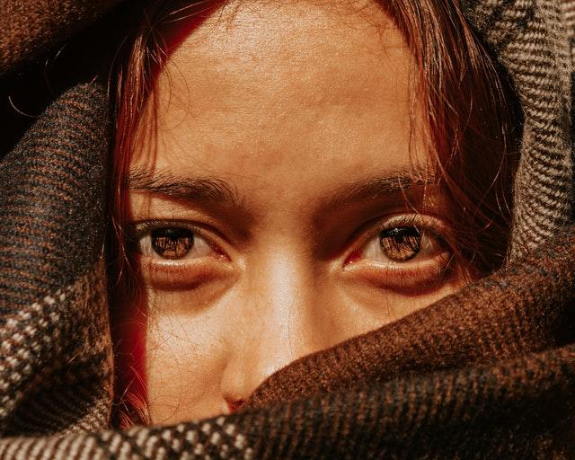 zbliżenie na oczy opalonej kobiety w rozpuszczonych włosach, która ma chustę na głowie