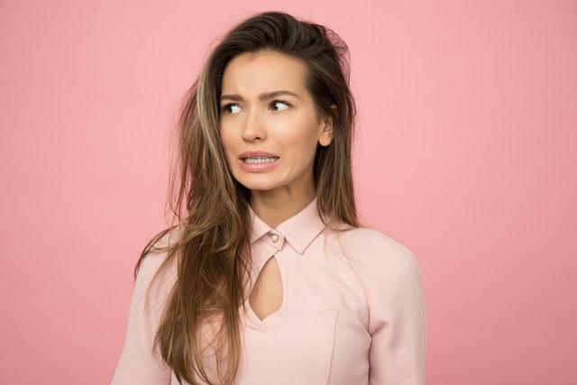 brunetka w długich włosach stoi na tle różowej ściany i ma zaskoczoną minę