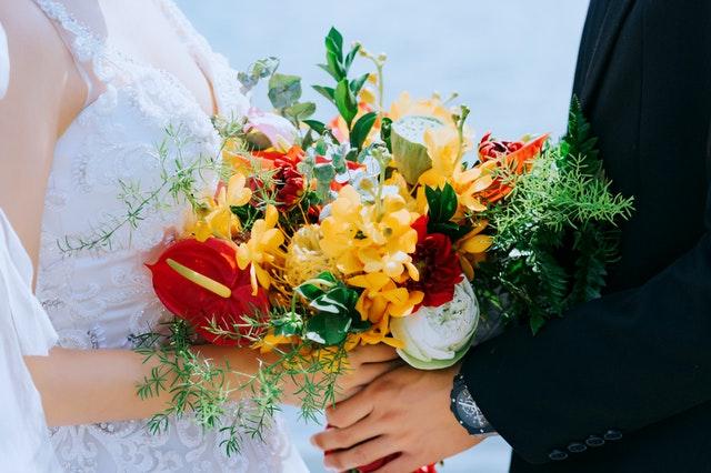 bukiet weselny żółto-czerwony trzymany przez pannę młodą i pana młodego