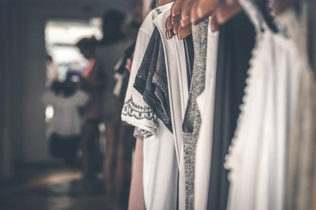 ubrania białe, szare i czarne powieszone na wieszaku