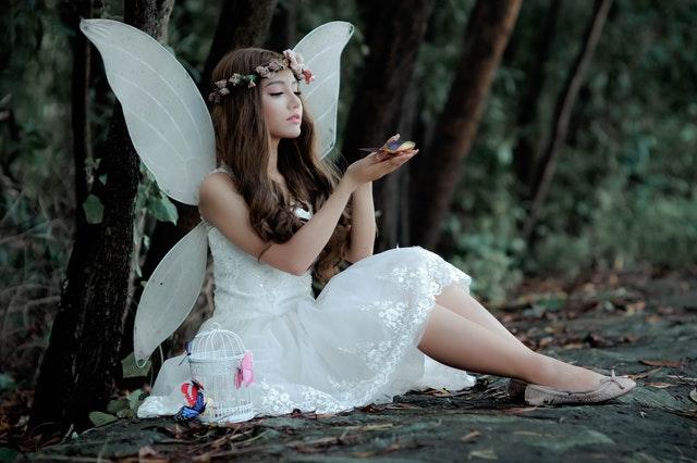 dziewczyna w białej letniej sukience siedzi na ziemi a na plecach ma skrzydła