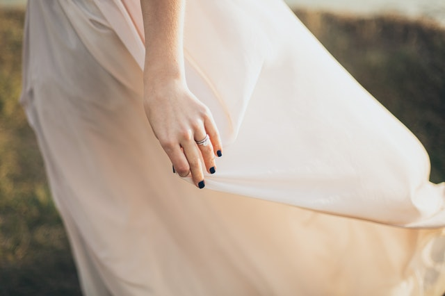 brzoskwiniowa suknia ślubna a na jej tle dłoń z czarnymi paznokciami
