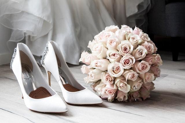białej szpilki na białej podłodze a obok różowy bukiecik