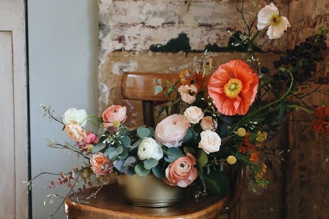 duży bukiet kolorowych kwiatów stojących na krzesełku