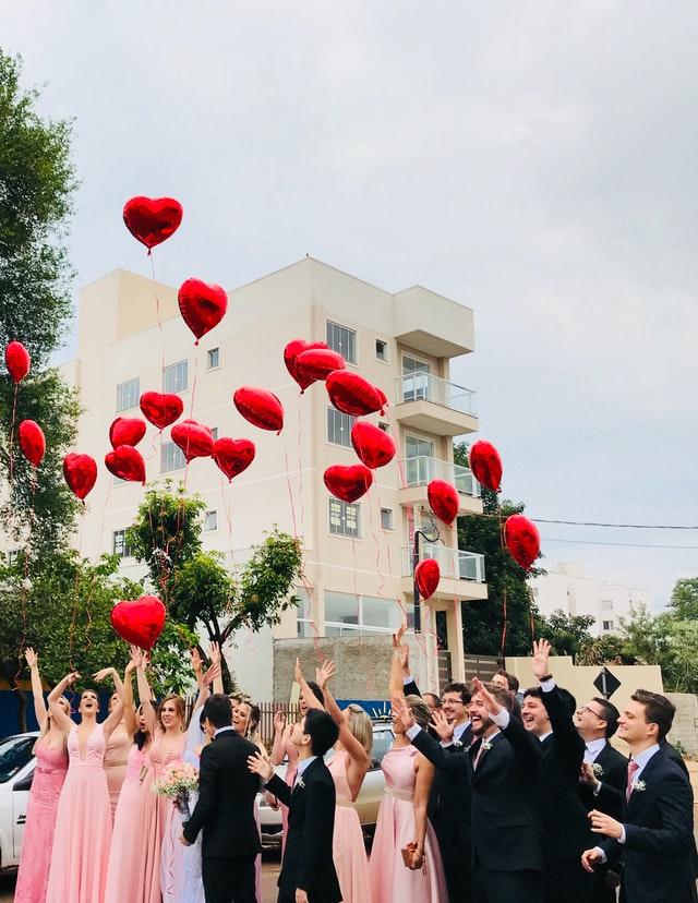 goście weselni i para młoda wypuszczają balony w kształcie serc