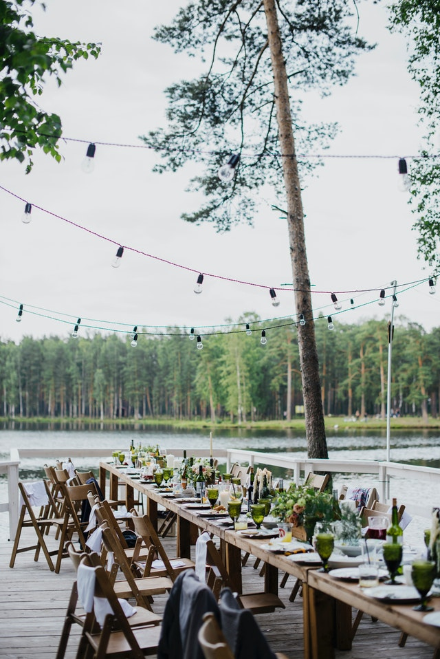 stół drewniany z talerzami i jedzeniem stojący nad jeziorem